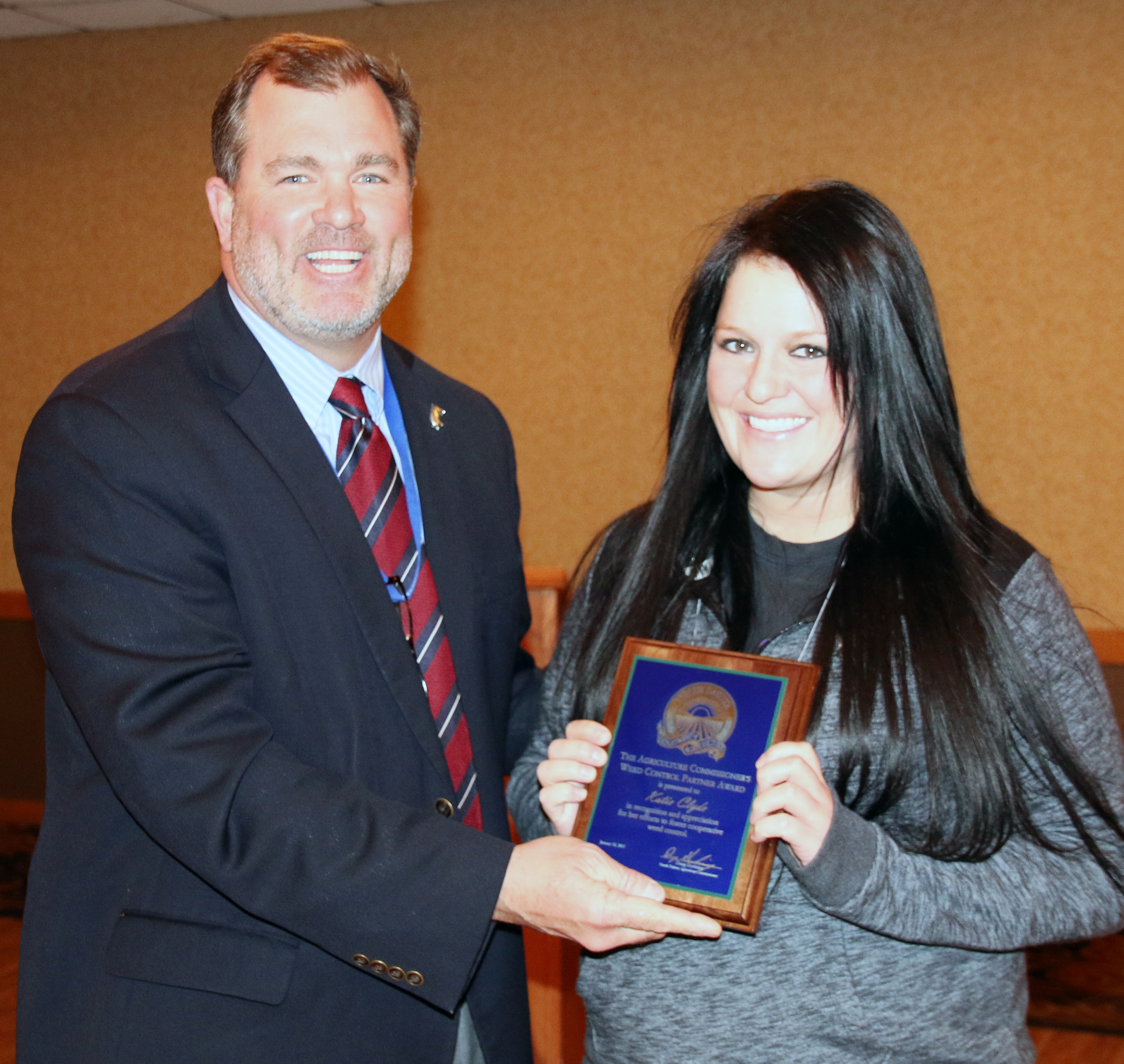 Deputy Agriculture Commissioner Tom Bodine, L, presents the award to Katie Clyde