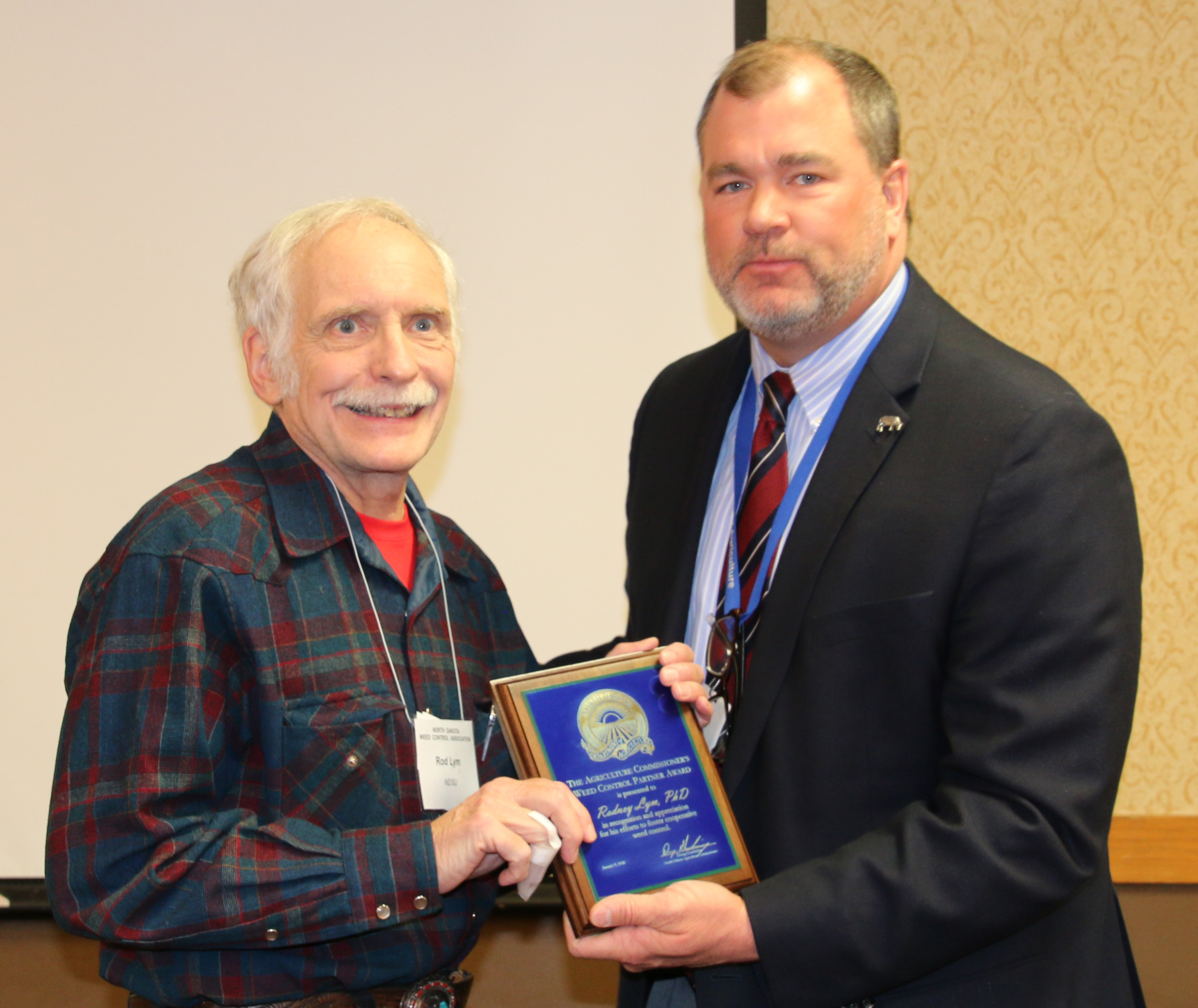 Deputy Commissioner Tom Bodine presents the award to Dr. Rodney Lym